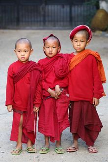 Three young Buddhist monks at a temple in Amarapura, Mandalay, Myanmar (Burma)