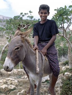 A boy rides home after school on a donkey in the Homhil Mountains