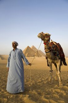 A camel driver stands in front of the pyramids at Giza, Egypt