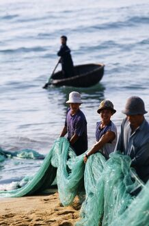 Carrying fishing nets up the beach after the day's work