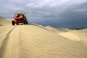 A dune buggy on the sand dunes bordering the city of Ica