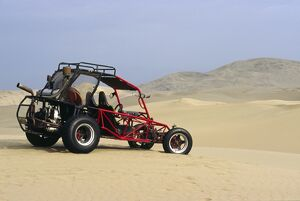 A dune buggy sits in the desert expense of Peru's