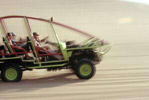 A dune buggy speeds tourists acoss through the sand