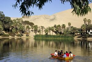 A family rows out onto the oasis lagoon of Huacachina