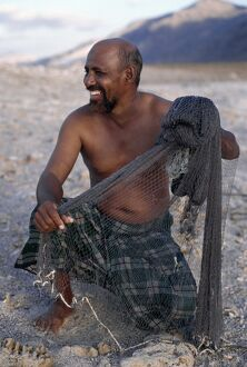 A fisherman near Di Hamri with his weighted throwing net