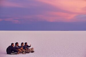 A group of tourists sit on the great expanse of salt