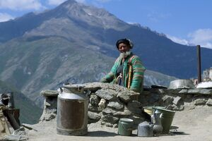 An old man sits beside the dusty road with his pots and milk churn, at Nometkun