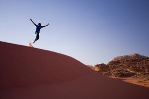 Person jumping off sand dune