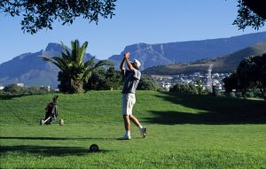 A player tees off at the golf course at Green Point overlooked by Table Mountain