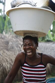A Sao Tomense woman laughs while carrying her washing up on her head