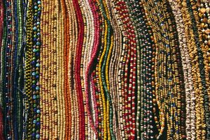 Strings of colourful beads are laid out for sale at