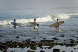 Surfers head into the surf at Mancora on the northern coast of Peru