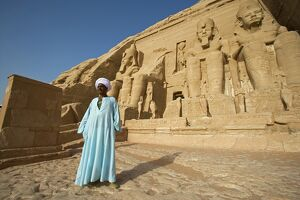 A temple guardian stands in front of the facade of Abu Simbel