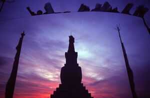 Tibetan Buddhist stupa and prayer flags silhouetted against sunset