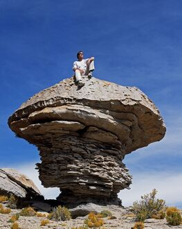 A tourist sits on top of a massive wind-eroded boulder