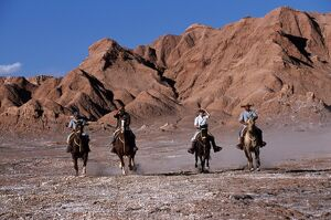 Tourists horse riding amongst the wind-eroded peaks