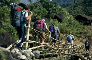 Trekkers crossing temporary bridge