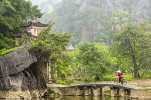 oriental flavours/woman crossing bridge bicycle temple tam coc
