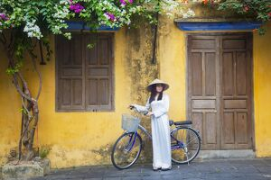 oriental flavours/woman wearing ao dai dress bicycle hoi unesco