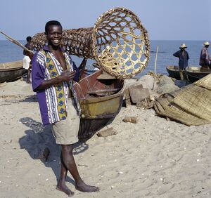 A young man carries a wicker fish trap