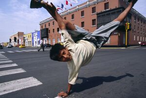 A youth performs an armstand on the streets of Trujillo