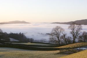 Valley mist over Windermere at dawn in the Lake District UK