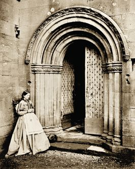 View of lady outside the North cloister doorway at Melrose Abbey. Date: 1866