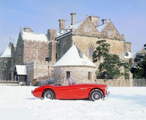 Austin Healey 100 in snow in front of Palace House