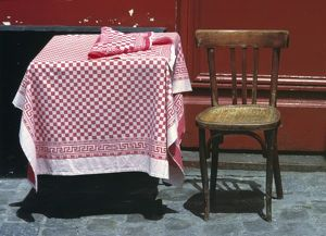 Europe, France, Paris. A sidewalk table for one welcomes a diner in the Montmartre