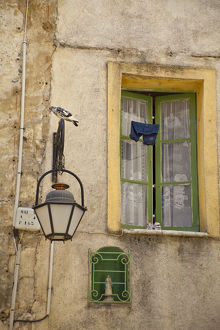 France, Provence, Vence. Child's trousers and shoes drying outside a home's window