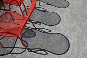 Red wire chairs shadows on concrete