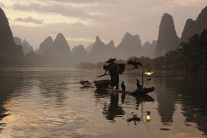 Traditional Chinese fisherman with cormorants on Li River at sunrise, near Guilin, China