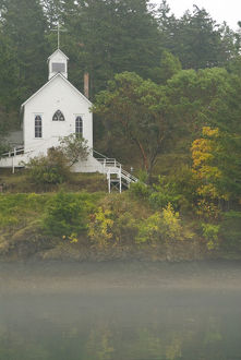 USA, WA, San Juan Island. Fall color and fog accent quaint Roche Harbor chapel