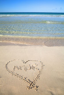Vieques, Puerto Rico - A heart is drawn in the sand of a beach with the word 'amor&#39