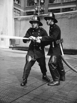 Firefighters taking part in a hose training drill