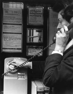 Woman dialling 999 in a public telephone box, London