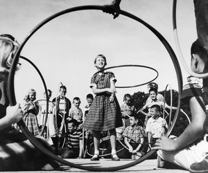 A 10-year-old girl shows off her hula hoop skills to her classmates, c1950s.