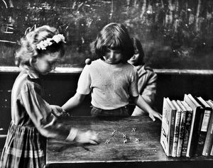 Two 5th grade girls playing jacks on the teacher's desk before school in Clairfield, Tennessee. Photograph by Jack Corn, 1964.
