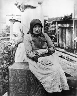 ALASKA: ESKIMO WOMAN. A seated Eskimo woman with totem pole sculptures behind her