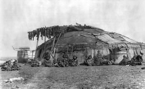ALASKA: ESKIMOS, c1897. A group of Eskimos seated outside a large circular house on St