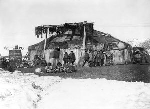 ALASKA: ESKIMOS, c1898. A group of Eskimos in front of a large house, with furs