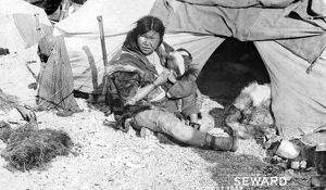 ALASKA: ESKIMOS, c1907. An Eskimo mother sitting outside a tent breast-feeding her child