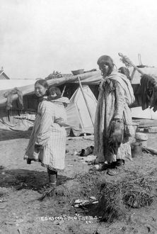 ALASKA: ESKIMOS, c1916. Two Eskimo mothers standing outside their tents, each carrying