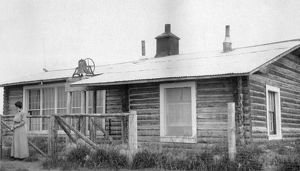 ALASKA: LOG CABIN. A woman standing in front of a log cabin in Fairbanks, Alaska