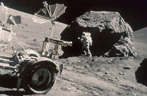 APOLLO 17, DECEMBER 1972: Front of Lunar Rover and Schmitt working by large boulder.