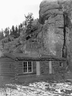 ARIZONA: LOG CABIN, c1908. Log cabin with a thatched roof in front of a large rock