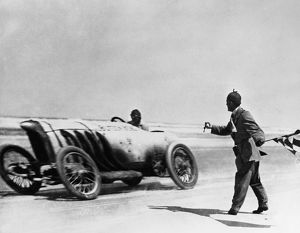 AUTO RACING, 1910. American automobile racer Barney Oldfield setting a record speed of 131