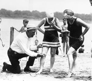BATHING SUITS, 1922. A Public Buildings and Grounds officer measures women's