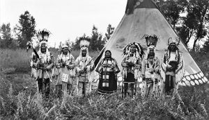 BLACKFOOT SINGERS, c1913. A group of Blackfoot men and one woman singing in front of a tepee