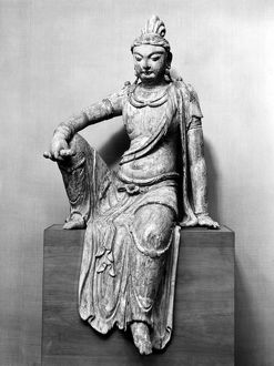 The bodhisattva Guanyin in the 'royal ease' position. Wood with traces of polychrome